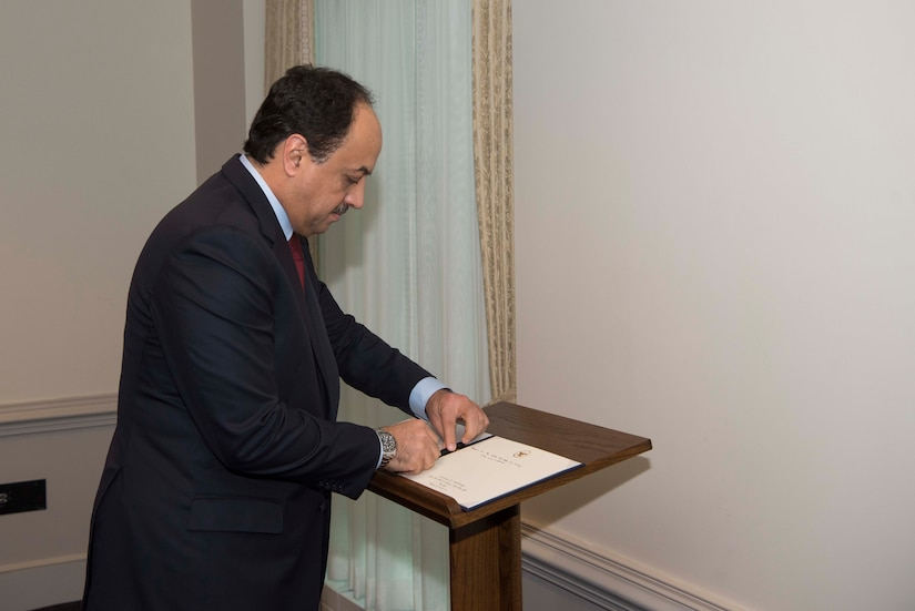 Qatar defense minister signs book.
