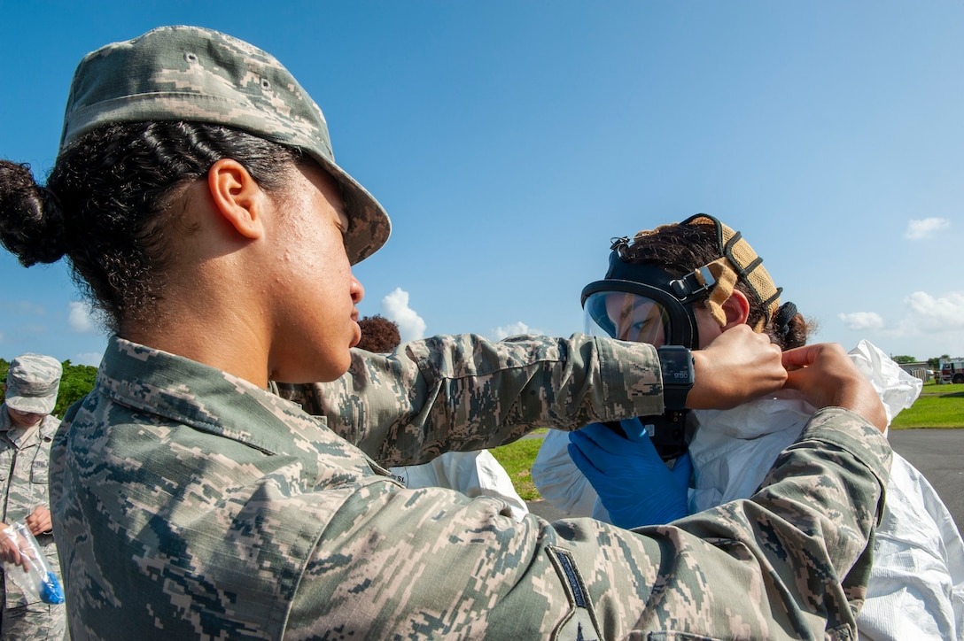 U.S. Air Force Airman Georgia Knight, 18th Aerospace Medicine Squadron bioenvironmental engineering technician, assists an Airman into a level-A suit during a fuel spill exercise at Kadena Air Base, Japan, Oct. 25, 2019. The level-A suit is the highest level protection against vapors, gases, mists and particles, which consists of a fully encapsulating chemical entry suit with a self-contained breathing apparatus. It's protects Airmen from hazardous material and harmful environments. (U.S. Air Force photo by Naoto Anazawa)