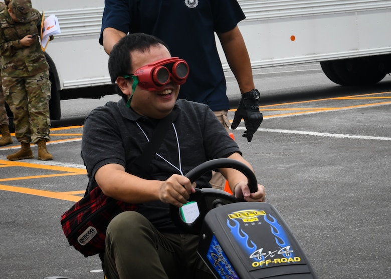 Kazunori Uehara, Twitter Tour visitor, drives a go-cart while wearing drunk goggles during a drunken driving prevention demonstration at Kadena Air Base, Japan, Nov. 4, 2019. Visitors were selected based on when they subscribed to the 18th Wing Twitter page and a brief application process. (U.S. Air Force photo by Staff Sgt. Benjamin Raughton)