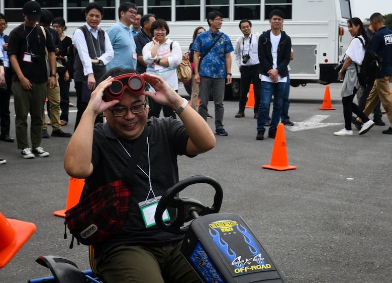 Kazunori Uehara, Twitter Tour visitor, drives a go-cart while wearing drunk goggles during a drunken driving prevention demonstration at Kadena Air Base, Japan, Nov. 4, 2019. Uehara was given drunk goggles to simulate driving under the influence of alcohol. Other demonstrations included using beer and mouthwash to show alcohol's effect on a breathalyzer. (U.S. Air Force photo by Staff Sgt. Benjamin Raughton)