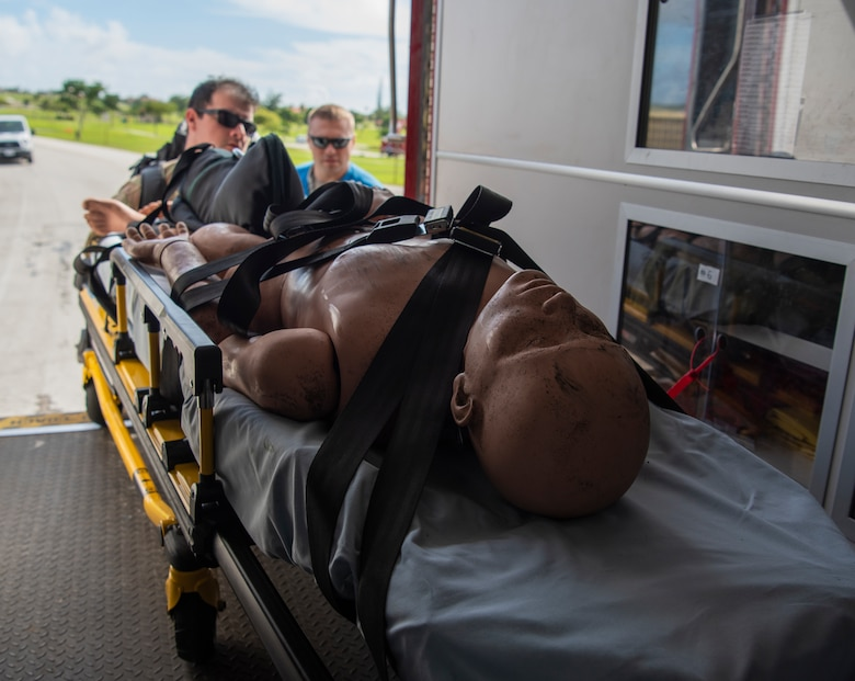Staff Sgt. Antonio Sixto (left), 36th Medical Operation Squadron paramedic and Tech. Sgt. Daniel Shimanski, 36th MDOS independent duty medical technician, load a mannequin into an ambulance during a fuel spill exercise on Andersen Air Force Base, Guam, Nov. 6, 2019.