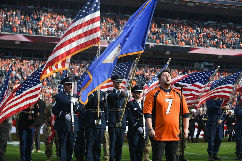 U.S. military service members stand at attention as Zach Kononov sings the national anthem, before the Denver Broncos Salute to Service game, at Empower Field at Mile High in Denver Nov. 3, 2019.