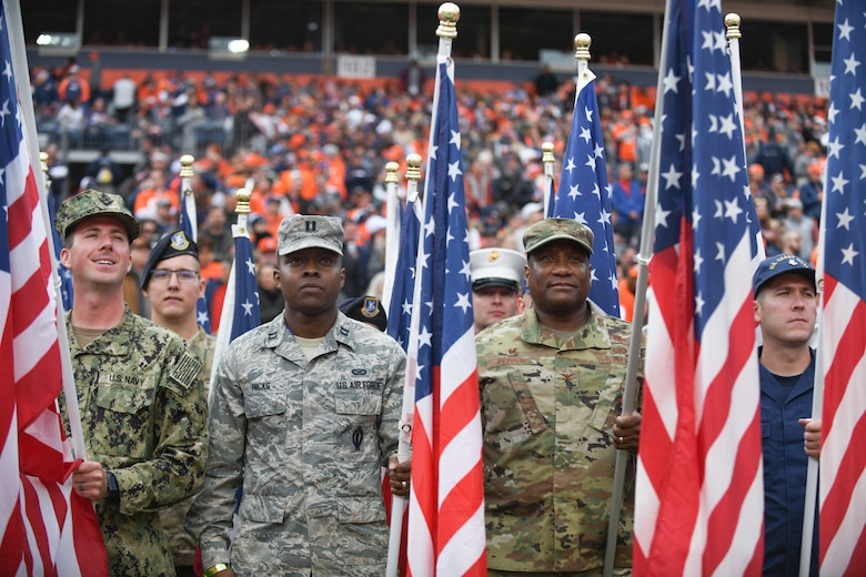 U.S. military service members hold American flags before the Denver Broncos Salute to Service game at Empower Field at Mile High in Denver, Nov. 3, 2019.