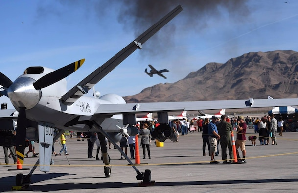 An MQ-9 Reaper assigned to the 432nd Wing/432nd Air Expeditionary Wing rests on the flightline as a A-10 Thunderbolt II flies overhead at the 2017 Aviation Nation Air and space Expo, Nov. 10, 2017, at Nellis Air Force Base, Nev. More than 165,000 spectators attended the event and celebrated the U.S. Air Force's 70th birthday. (Photo by Senior Airman Christian Clausen)