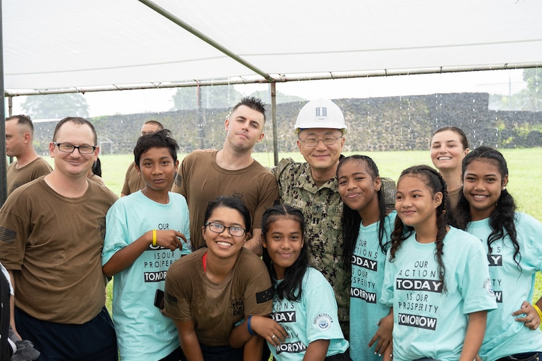 191104-N-WA745-1024 KOLONIA, Pohnpei (Nov. 4, 2019) Seabees deployed with Naval Mobile Construction Battalion (NCMB) 5's Detail Pohnpei and members of the Sokehs Youth Choir pose for a photograph outside the Kolonia Gymnasium during the Federated States of Micronesia Independence Day celebration in Pohnpei Nov. 4.  The Seabees are providing humanitarian aid to the local community by finishing a medical facility, Nan U Dispensary, and performing renovations to multiple schools across the island. NMCB-5 is deployed across the Indo-Pacific region conducting high-quality construction to support U.S. and partner nations to strengthen partnerships, deter aggression, and enable expeditionary logistics and naval power projection.