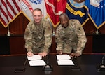 Two lieutenant generals sign an agreement.