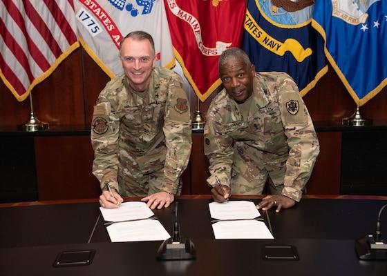 Two lieutenant generals sign an agreement.