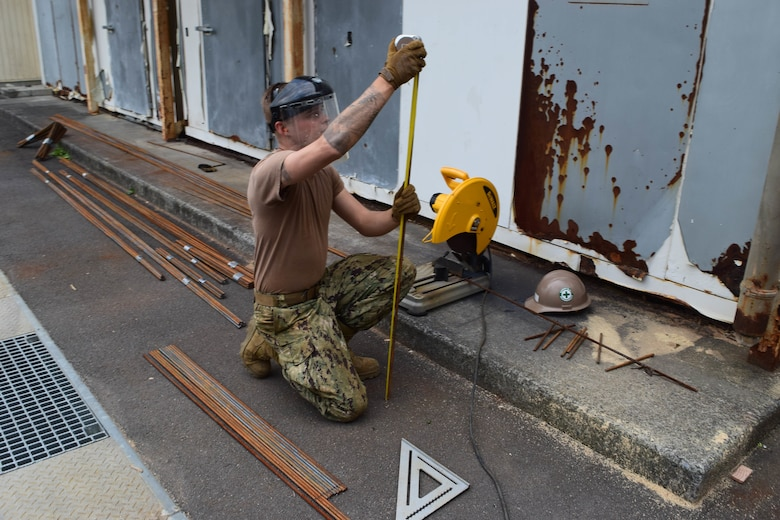 191025-N-EO124-0024 IWAKUNI, Japan (Oct. 25, 2019) Steelworker Constructionman Garrett Wells, from Yale, Michigan, deployed with Naval Mobile Construction Battalion (NMCB) 5's Detail Iwakuni, prefabricates reinforced steel for an environmental trash enclosure project.  NMCB-5 is deployed across the Indo-Pacific region conducting high-quality construction to support U.S. and partner nations to strengthen partnerships, deter aggression, and enable expeditionary logistics and naval power projection.