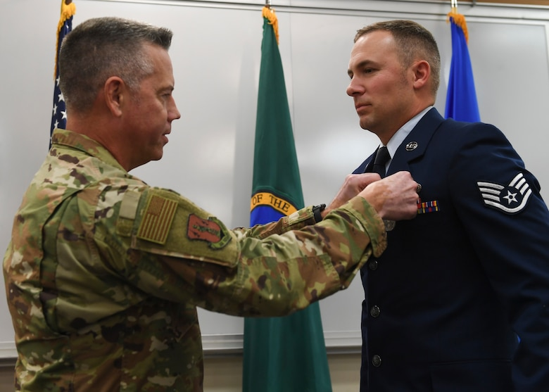 Brig. General Jeremy Horn, Washington Air National Guard commander, pins the Washington State Guardsman Medal on Staff Sgt. Jonathan Tinsley, 116th Air Support Operations Squadron Tactical Air Control Party, Nov. 2, 2019, at Camp Murray, Washington. Tinsley received the medal for stopping an attacker from assaulting two people.