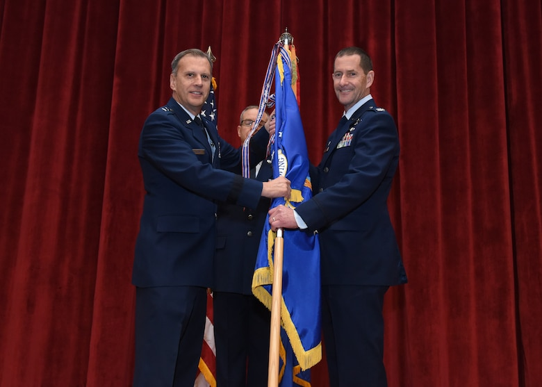 Maj. Gen. Randall A. Ogden, 4th Air Force commander, passes the 911th Airlift Wing guidon to the incoming commander, Col. John F. Robinson, during an assumption of command ceremony at Moon Area Middle School in Coraopolis, Pennsylvania, Nov. 2, 2019.