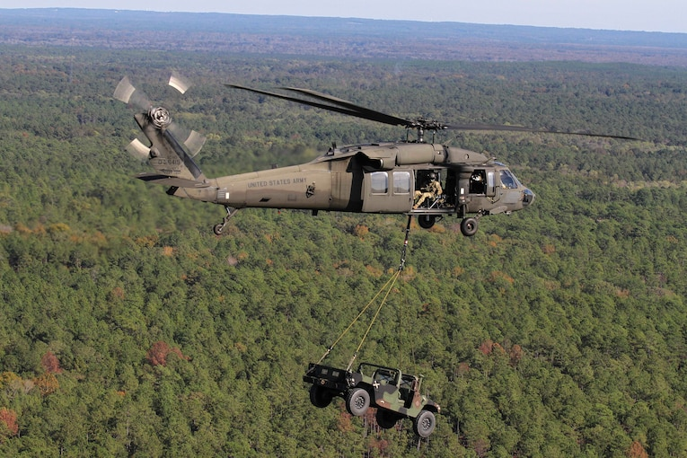 A helicopter carries a military vehicle while flying over trees.