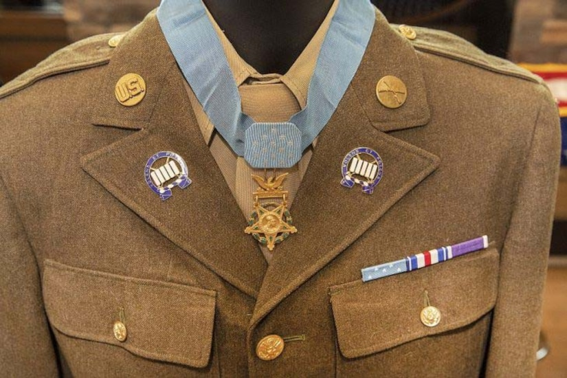 A mannequin holding a World War II-era Army dress uniform is decorated with a Medal of Honor.