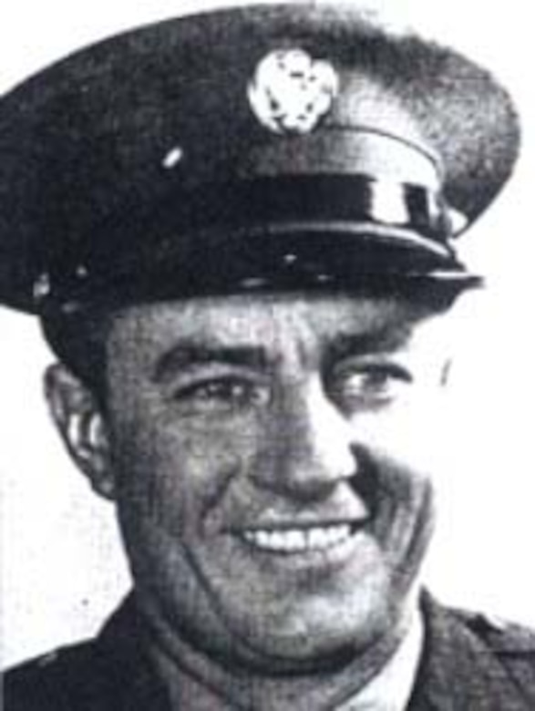 A man wearing an Army dress cap smiles for a photo.