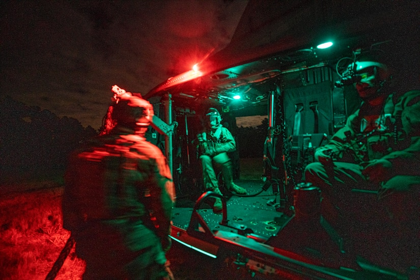 Airmen board a Marine Corps helicopter at night.