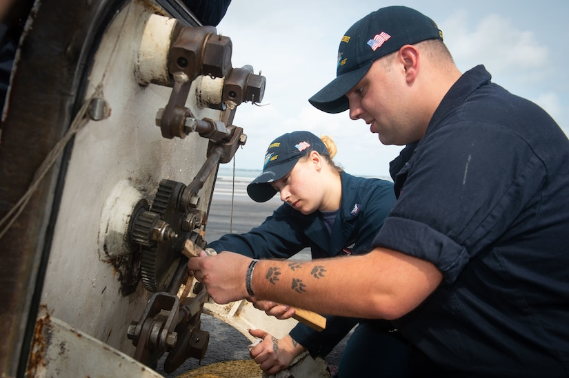 Two sailors work on equipment.