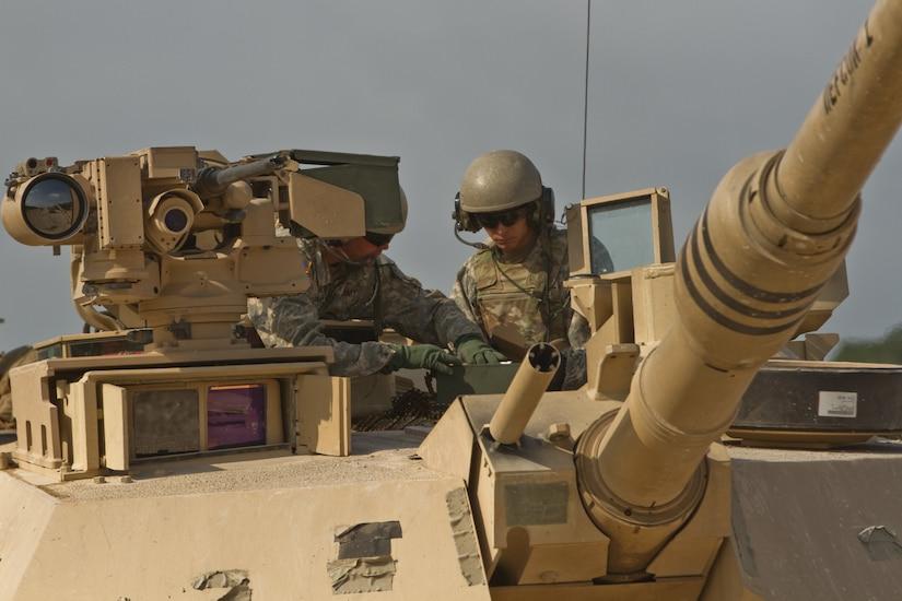 Crewman atop a tank converse.
