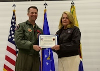 Col. Stephen Jones, 432nd Wing/432nd Air Expeditionary Wing commander, and Susan Sullivan, 432nd WG/432nd AEW civic leader, hold a certificate