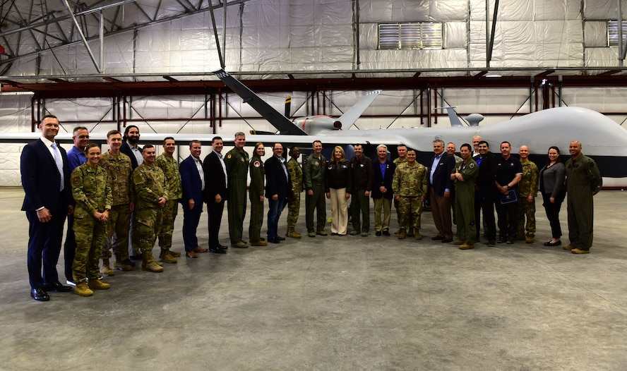 Members of Creech Air Force Base and the Las Vegas community stand in a line for a group photo near an MQ-9 Reaper