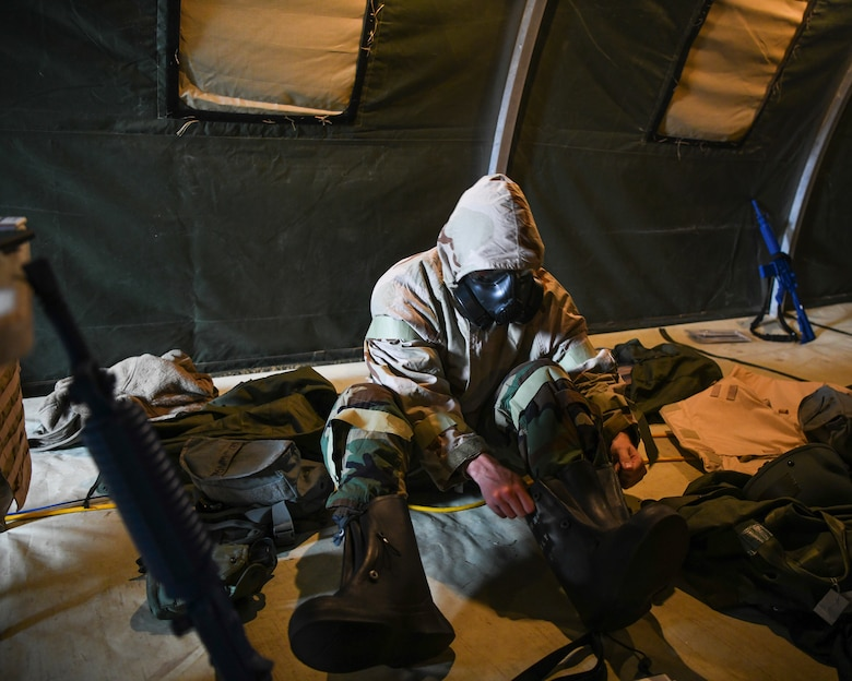 U.S. Air Force Staff Sgt. Garrett Sullivan, 628th Air base Wing Public Affairs photojournalist and exercise Unit Control Center dispatcher, dons Mission Oriented Protective Posture gear in response to a chemical attack exercise during Palmetto Challenge at McEntire Joint National Guard Base, S.C., Nov. 3, 2019. The goal of the exercise was to develop and maintain full-spectrum readiness and ensure JB Charleston's Airmen were ready for rapid mobilization and able to support Air Mobility Command and DOD priorities. Both active-duty and reserve Airmen from the 628th Air Base Wing, 437th Airlift Wing and 315th Airlift Wing came together to train in operating in an austere environment. More than 140 Airmen took part in the global mobilization readiness exercise at McEntire Joint National Guard Base, and Pope Army Airfield, S.C.