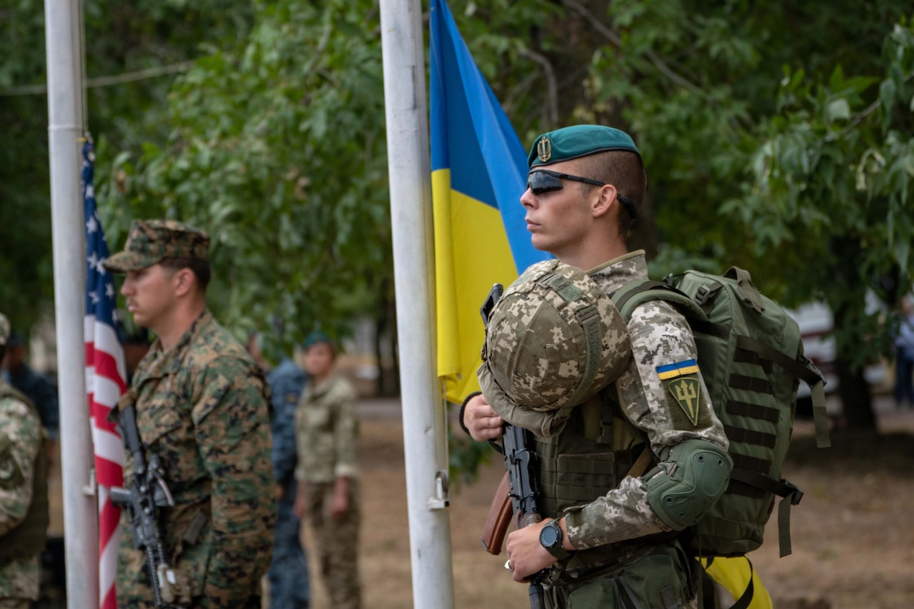 A service member in camouflage uniform stands next to the Ukranian flag.