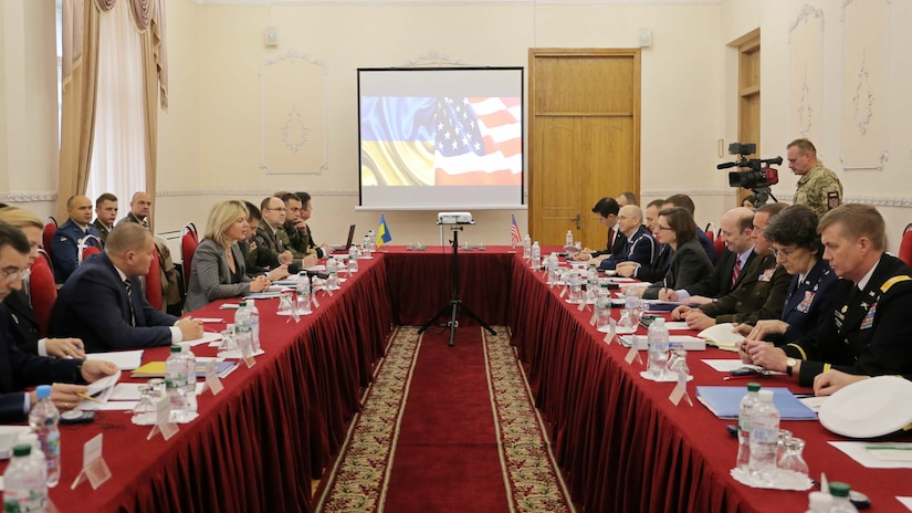 People in business suits and military uniforms sit at long tables facing each other.