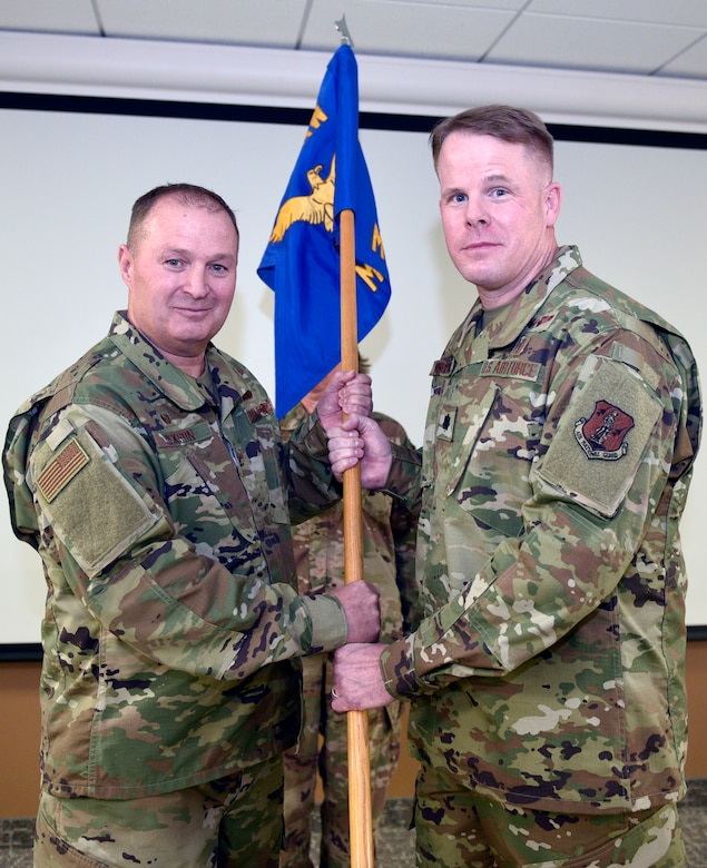 Lt. Col. Jonathan Bingham accepts the 120th Medical Group guideon from Col. Buel Dickson, 120th Airlift Wing Commander, as part of the change of command ceremony Nov. 3, 2019 here. Bingham was selected as the new commander of the 120th MDG.