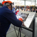 PASCAGOULA, Miss. (Nov. 7, 2019) Ingalls Shipbuilding welder James Ellis welds Ship Sponsors Ruby Lucas and Catherine B. Reynolds' initials into a steel plate during a keel authentication ceremony for the future USS Jack H. Lucas (DDG 125) at Huntington Ingalls Industries Pascagoula shipyard Nov. 7, 2019. DDG 125 is the first ship to be named for Jack H. Lucas. During World War II, Lucas, then a private first class in the Marine Corps, received the Medal of Honor at age 17 for heroism above and beyond the call of duty during the Battle of Iwo Jima.