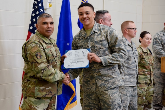Col. Anthony Puente, 982nd Training Group commander, presents Airman Ahstawn Wilson, 22nd Maintenance Squadron crew chief, with a Certificate of Training during the Mission Ready Airmen program graduation Nov. 5, 2019, at McConnell Air Force Base, Kan. The MRA program took 56 academic days to complete. (U.S. Air Force photo by Airman 1st Class Marc A. Garcia)