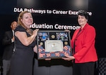 Woman accepts plaque from another woman