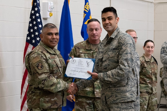Col. Anthony Puente, 982nd Training Group commander, presents Airman Antonio Acunaback, 22nd Maintenance Squadron crew chief, with a Certificate of Training during the Mission Ready Airmen program graduation Nov. 5, 2019, at McConnell Air Force Base, Kan. Four Airmen graduated from McConnell's first Mission Ready Airmen program. (U.S. Air Force photo by Staff Sgt. Alexandria Brun)