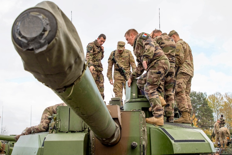 U.S. and French soldiers stand on top of a tank and examine its parts.