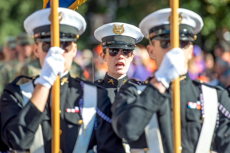 An Army ROTC cadet calls out as two cadets march in front of her.