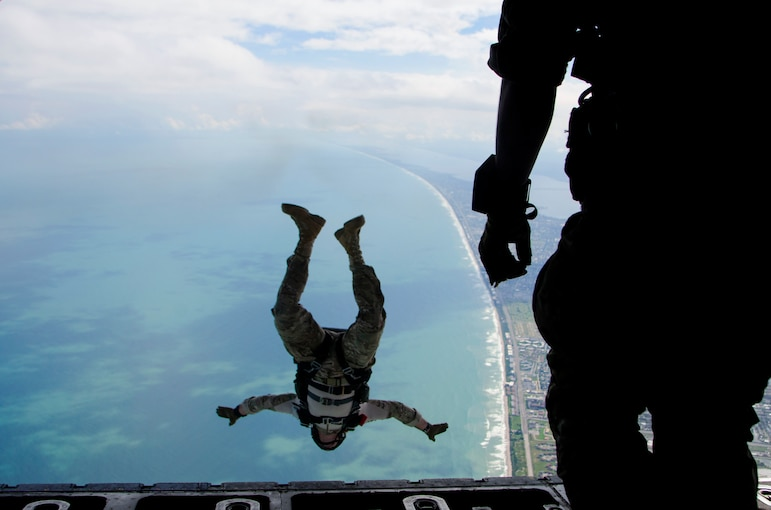 An airman falls upside-down over water as another watches from an open aircraft.