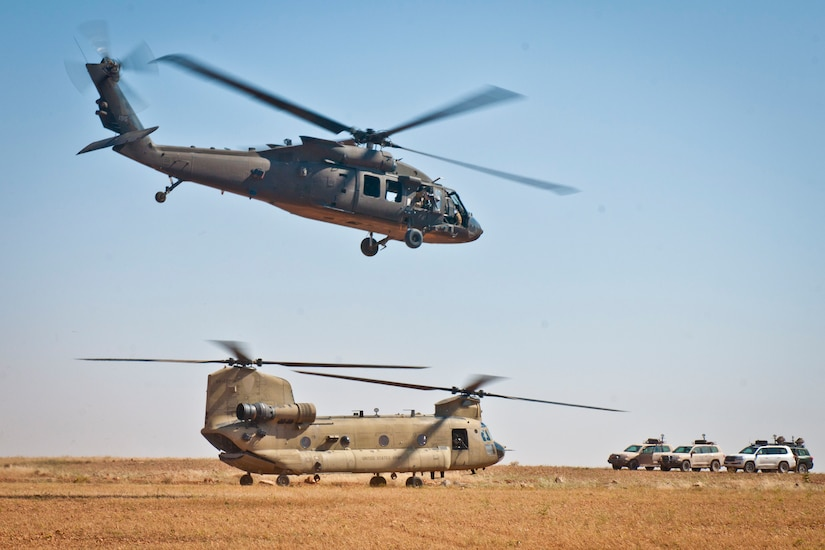 In a desert environment, a helicopter flies over the sands. Another helicopter sits on the ground near multiple vehicles.