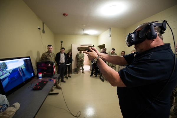 Civic leader David Radcliffe (right), President of the Radcliffe Group, Keller Williams Realty Southwest, tries a virtual reality simulator at the Security Forces mock Air Base and firearms simulators building, Nov. 7, 2019, at Joint Base San Antonio-Medina Annex, Texas