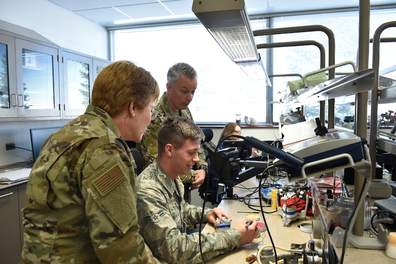 Lt. Gen. Dorothy Hogg, U.S. Air Force Surgeon General, and Chief Master Sgt. Steve Cum, Medical Enlisted Force and Enlisted Corps chief, watch as an Airman works through a dental project at the Area Dental Laboratory on Peterson Air Force Base, Colorado, Nov. 1, 2019. While visiting the Peterson Dental Lab, Hogg and Cum had the chance to see how different molds, implants, and dental pieces are made on a daily basis. (U.S. Air Force photo by Airman Alexis Christian)