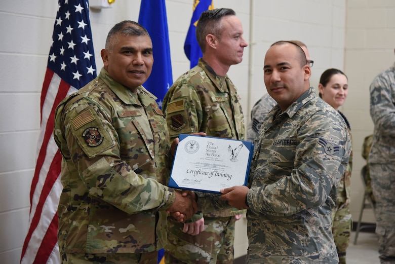 Col. Anthony Puente, 982nd Training Group commander, presents Airman 1st Class Francisco Ramirez, 22nd Maintenance Squadron crew chief, with a Certificate of Training during the Mission Ready Airmen program graduation Nov. 5, 2019, at McConnell Air Force Base, Kan. The Mission ready Airmen program allows Airmen to have a deeper understanding and knowledge of the KC-46 Pegasus before reaching their respective units. (U.S. Air Force photo by Airman 1st Class Marc A. Garcia)