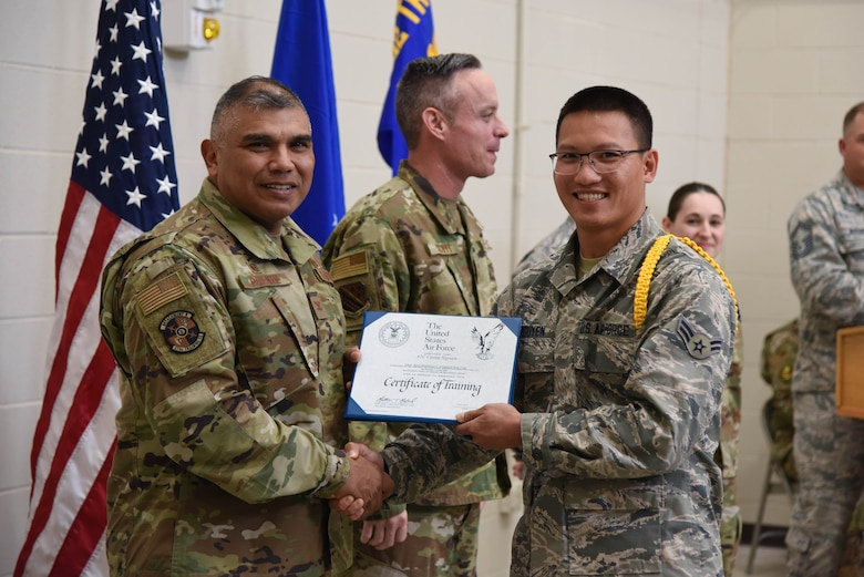 Col. Anthony Puente, 982nd Training Group commander, presents Airman 1st Class Cuong Nguyen, 931st Maintenance Squadron crew chief, with a Certificate of Training during the Mission Ready Airmen program graduation Nov. 5, 2019, at McConnell Air Force Base, Kan. Class 190021 was the first class to graduate as qualified KC-46 Pegasus crew chiefs. (U.S. Air Force photo by Airman 1st Class Marc A. Garcia)