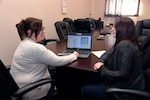 Procurement Analyst Erin Clore (left) and Contracting Officer Kayla DesVoignes discuss the features of the new online tool helping staff members ensure they use the latest information and comply with all of the rules and regulations for contracts.