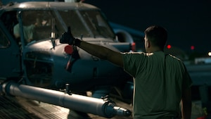 A U.S. Air Force Airman directs the unloading of an HH-60 Pave Hawk helicopter assigned to the 305th Rescue Squadron, Davis-Monthan Air Force Base, Ariz., from a C-5 Super Galaxy assigned to the 512th Airlift Wing, Dover Air Force Base, Del., at MacDill Air Force Base, Fla., Nov. 6, 2019.