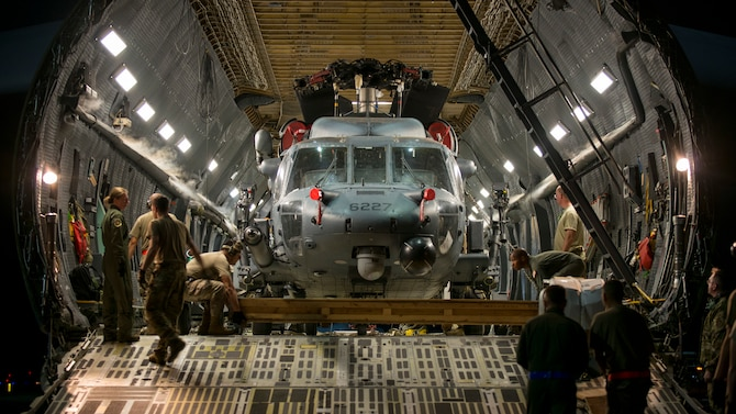 Aircrew prepare to unload an HH-60 Pave Hawk helicopter assigned to the 305th Rescue Squadron, Davis-Monthan Air Force Base, Ariz., from a C-5 Super Galaxy assigned to the 512th Airlift Wing, Dover Air Force Base, Del., at MacDill Air Force Base, Fla., Nov. 6, 2019.