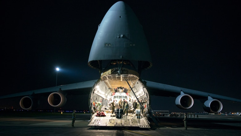 Aircrew prepare to unload an HH-60 Pave Hawk helicopter assigned to the 305th Rescue Squadron, Davis-Monthan Air Force Base, Ariz., from a C-5 Super Galaxy assigned to Dover Air Force Base, Del., at MacDill Air Force Base, Fla., Nov. 6, 2019.