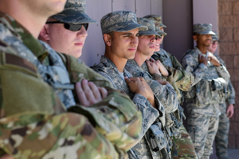 Eight Security Forces Airmen stand outside with their arms crossed