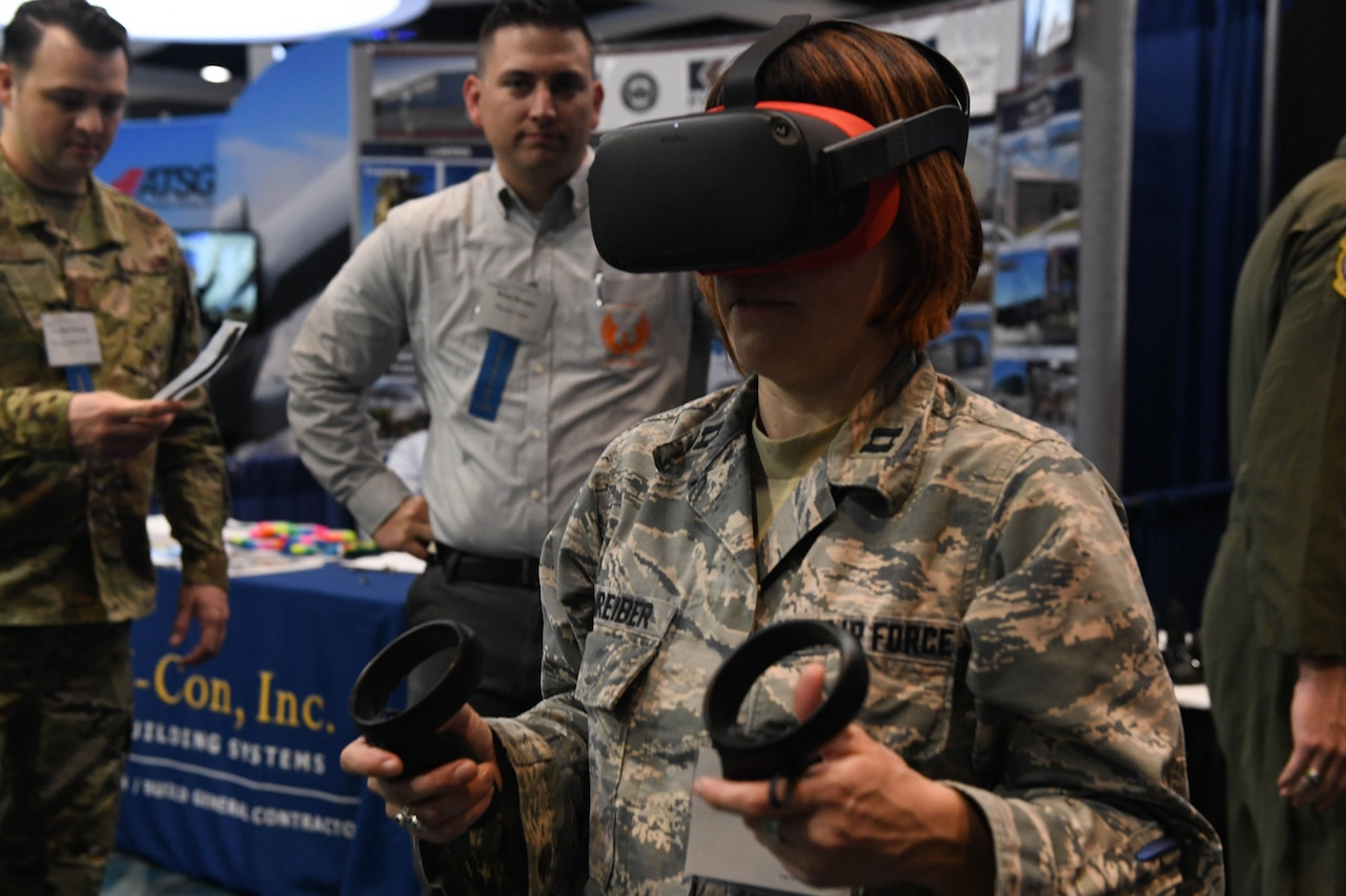 A female airman wearing virtual reality goggles holds two different handpieces. Two men at a booth in the background watch her.
