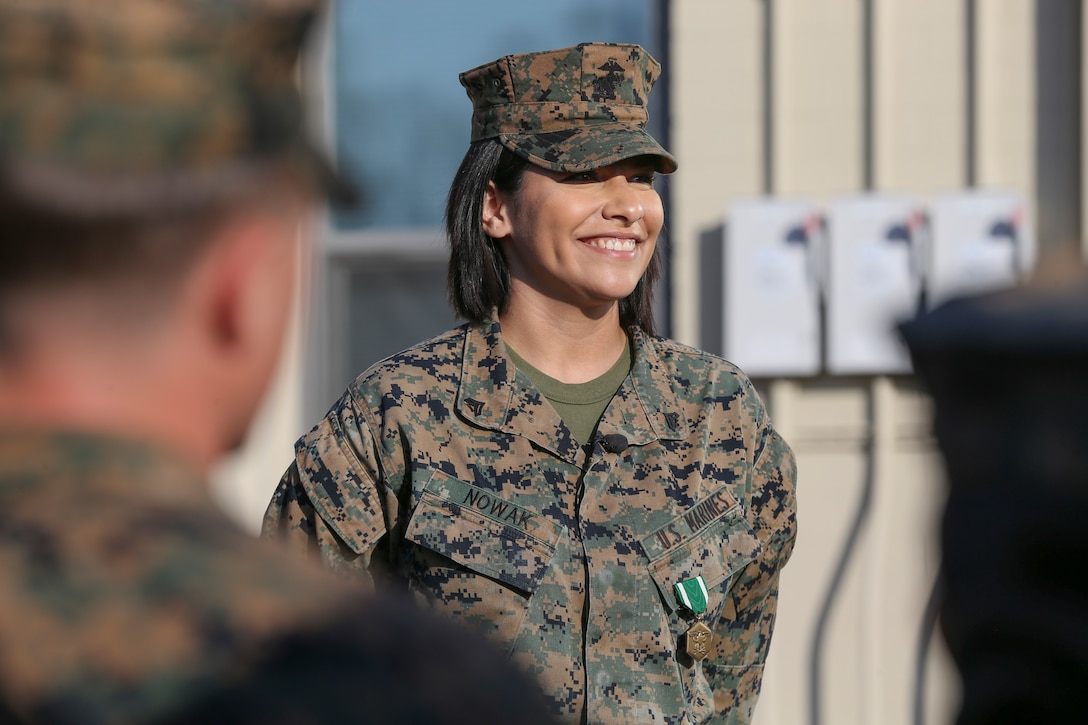 U.S. Marine Cpl. Alexandra Nowak, an administrative specialist with Alpha Company, Headquarters and Support Battalion, Marine Corps Installations West, Marine Corps Base Camp Pendleton, listens to Brig. Gen. Dan Conley, the commanding general for MCI-West, MCB Camp Pendleton, speak after he awarded her the Navy and Marine Corps Commendation Medal on Camp Pendleton, California, Nov. 6, 2019. Nowak received the award for her actions to save a family after a car crash on Interstate Highway 15. Nowak is a native of Forney, Texas.