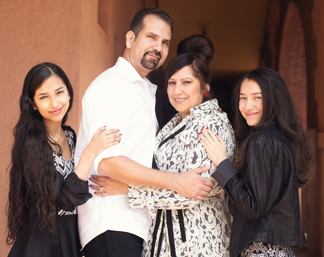 A family poses together with a mother, father and two daughters.