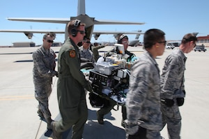 "During an engine-running offload, a litter-carry team moves a simulated critically ill patient out of a C-130J Super Hercules to a waiting ambulance bus during 349th Air Mobility Wing Air Force Specialty Code training June 6, 2015, at Travis Air Force Base, Calif. In preparation for the training, the 349th Aeromedical Evacuation Squadron transformed the four-engine tactical transport into a flying hospital. In turn, the CCATT teams from the 60th Surgical Operations Squadron and the 349th Aeromedical Staging Squadron established onboard what was essentially a portable intensive care unit dedicated to one very ill, simulated, ""patient."" The C-130 was from the California Air National Guard's 146th Airlift Wing, Channel Islands Air National Guard Station, California. (U.S. Air Force photo/Lt. Col. Robert Couse-Baker/Released)"
