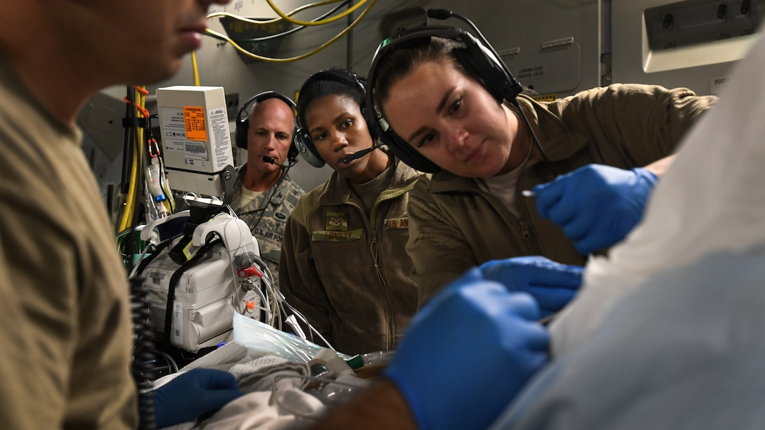 A critical care air transport team tends to a patient during a 20-hour direct flight from Bagram Airfield, Afghanistan, to San Antonio, Texas, Aug. 18, 2019. The service member was cared for by a joint service team of extracorporeal membrane oxygenation specialists, an aeromedical evacuation team as well as CCATT in order to maintain the highest level of care possible during transport. (U.S. Air Force photo by Airman 1st Class Ryan Mancuso)