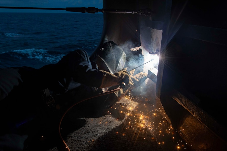 A sailor lies on a ship's deck to weld something through a panel at night.