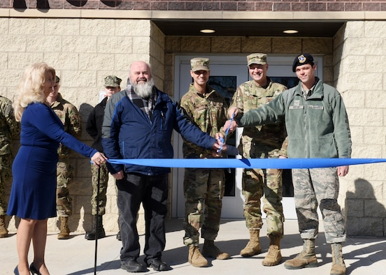 From left to right: Doug Shapland, 55th Civil Engineer Squadron project manager, Col. William Dayton, 55th Mission Support Group commander, Chief Master Sgt. Brian Thomas, 55th Wing command chief and Airman 1st Class Shane Potter, 55th Security Forces Squadron patrolman, cut a ribbon to mark the opening of Cobb Hall, the installation's newest dormitory, Nov. 7, 2019. The new 51,000 square foot, three-floor dormitory includes 30 module suites that can accommodate 120 Airmen. The new $18.8 million dormitory is named in honor of retired Chief Master Sgt. Lawrence A. Cobb.